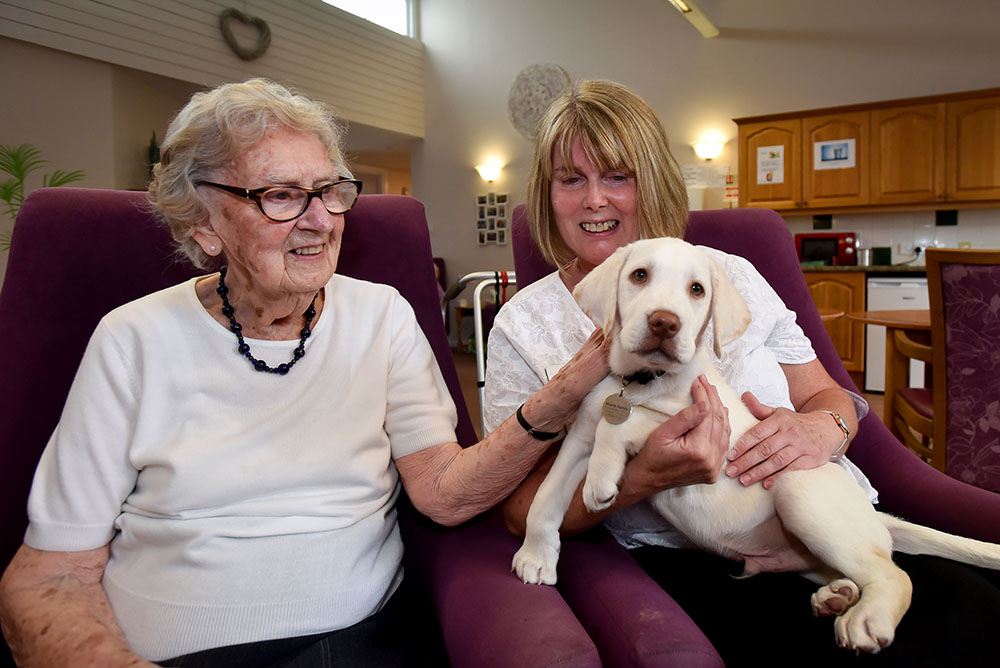 June Lambley and Denise Morris (Manager) with Charlie the puppy.