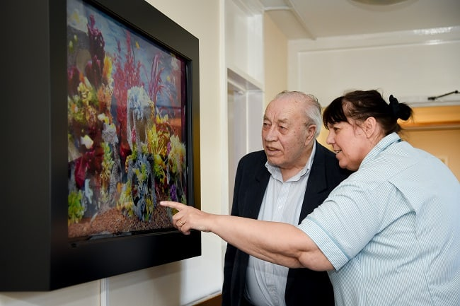 Bert Nicholson with carer Julie Bance checking out virtual fish tank